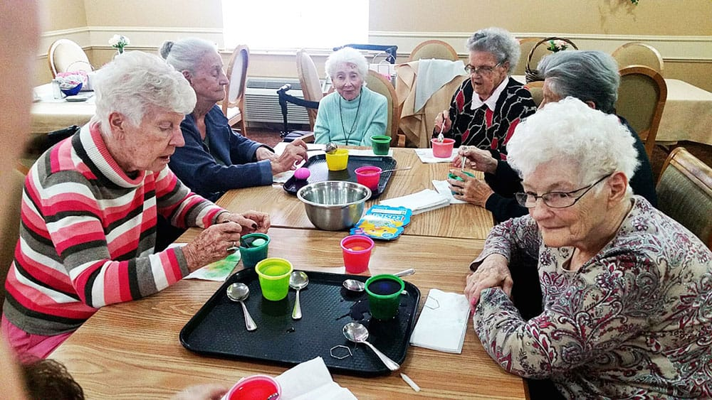 Six ladies at a table having fun dyeing Easter Eggs.