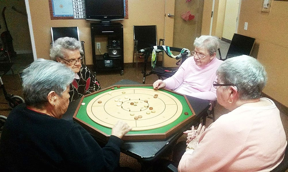 Seniors having fun playing a type of board game at a card table.