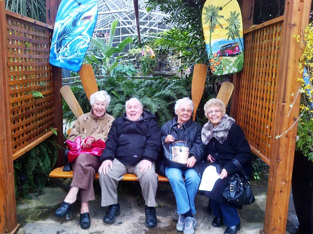 Four Cardinal Retirement Residents sitting together on a bench at the public gardens.