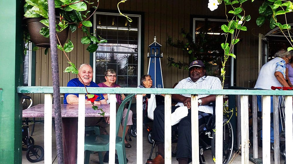 Some seniors from Cardinal Retirement residence sitting outside on the porch of a restaurant.