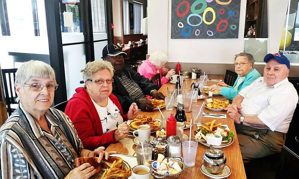 Seniors having fun eating lunch inside a restaurant.