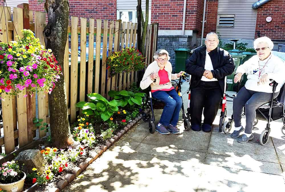 Three seniors from the Cardinal Retirement Residence sitting outside with their rollators.
