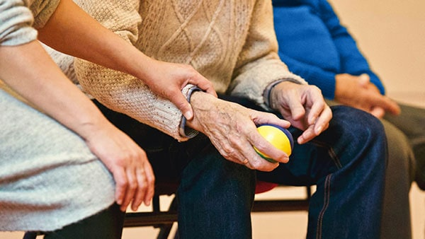 A PSW helping a man do hand exercises with a soft ball.