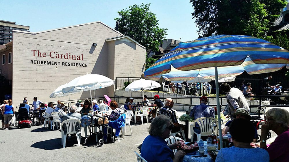 About eighty friends from Cardinal Retirement Residence outside, enjoying a sunny day BBQ with their family.