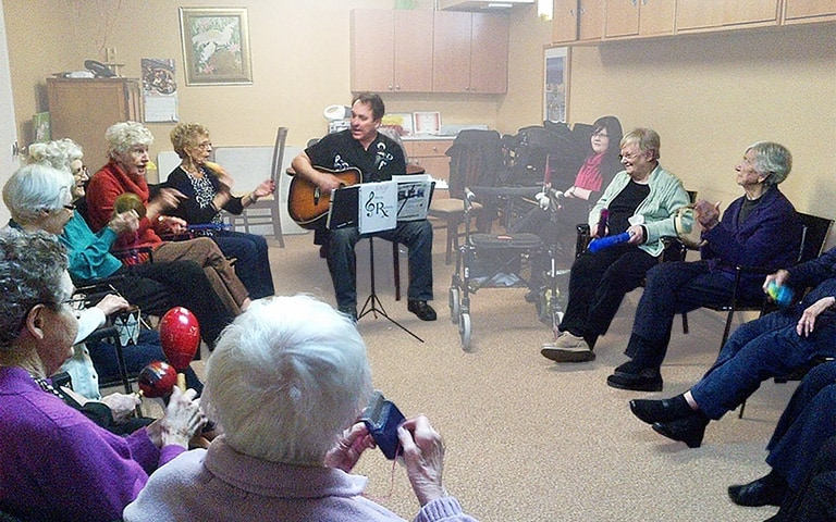 Group of Cardinal Retirement residents singing along to a man playing the guitar