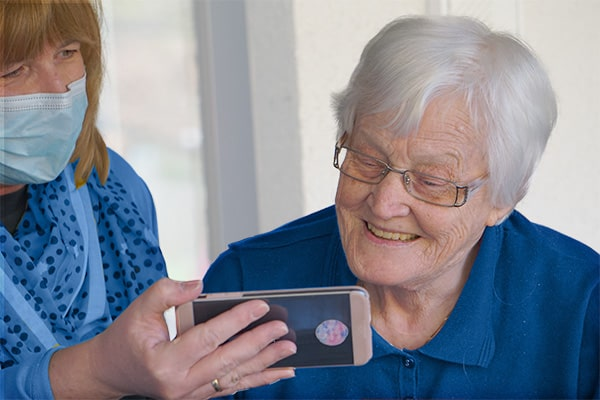 A woman showing a senior a mobile device