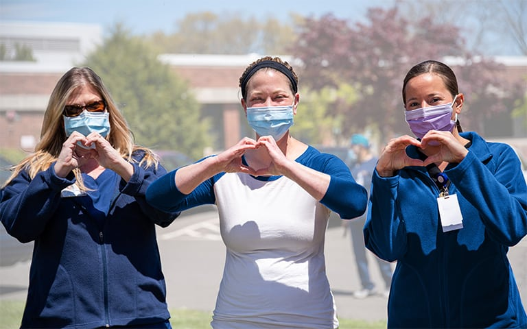 Three Personnel Support Workers wearing face masks and making the heart symbol with their hands.